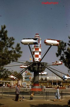 Disneyland guests take flight in the Astro Jets, which replaced Tomorrowland's Court of Flags. The Space Bar and a storybook sign advertising the Skyway are seen beyond, 1956. | stuff from the park