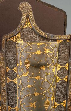 Persian char-aina cuirass, detail view, 17th century,(chahar-aina, chahar a'ineh). Literally the four mirrors. Four plates worn over a zirah (shirt of mail) in Persia, India and Central Asia. Rectangular or round plates, the two plates worn on the breast and back are considerably larger than those worn at the sides which had recesses for the arms. During the 16th c, char-aina were introduced in Persia, steel; inlaid with gold, H. 14.50 in. (36.8 cm) Diam. 13 in. (33 cm), Met Museum.