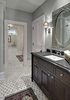 love the marble tile with the gray wall and white moulding and dark vanity. Needs two sinks though. This bathroom style would be my top choice for a master. Very lux.