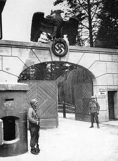 """Dachau Massacre -The gate shown in the photograph below is where """"the Germans were ready to surrender, not fight."""" It was about 75 yards from this gate, located on the southwest side of the Dachau complex, that 2nd Lt. Heinrich Wicker surrendered the Dachau concentration camp to Brig. Gen. Henning Linden of the 42nd Infantry Division. This photo was taken after the liberation; it shows two American soldiers guarding the gate."""