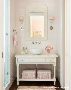 Melissa Haynes - Tres chic girl's bathroom features a nook clad in white beveled subway tiles lined with a cream bone inlay mirror illuminated by sconces with pink shades placed over a white washstand with shelf fitted with pink baskets topped with a bowl sink and wall mount sink.