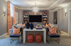 Orange and gray basement family room features walls clad in gray grasscloth wallpaper lined with a ...
