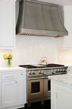 Amazing kitchen features white shaker cabinets paired with white quartz countertops and gray subway tile backsplash as well as French range hood paired with white marble herringbone backsplash over high-end gas range.