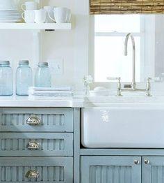 Fresh blue cupboards. Farmhouse sink. Bamboo shade.