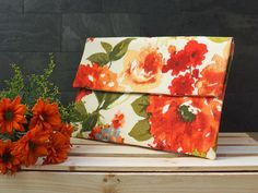 This envelope clutch is the perfect size to carry your phone, cards, keys, and basic essentials! The beige and orange floral fabric will be your