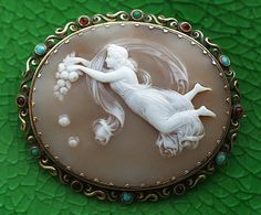 Aurore      Materials: shell, gold, garnets, turquoises  Date: ca. 1860  Origin of the cameo: England  Size of the cameo: 2 1/16 x 1 3/4   Size of the frame: 2 3/8 x 2