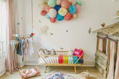 Une chambre d'enfant décorée d'un nuage de lampions colorés