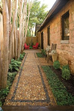 The pebbled border adds texture in this cozy side-yard path and patio. A pair of planters and a bench half-way down the path breaks up the space.