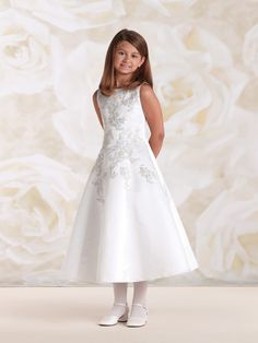 Sleeveless satin tea-length A-line dress accented with re-embroidered metallic lace appliqués on front and in back, covered buttons down back bodice, ideal as a First Communion dress or flower girl dress. Sizes: 4 – 14 Colors: White, Cream