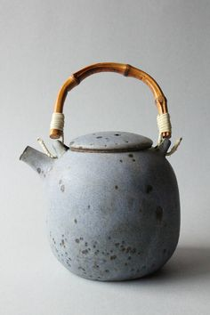 Mayumi Yamashita, matt glazed speckled blue teapot with bamboo handle. Black mica is mixed into the clay to create rusty spots.