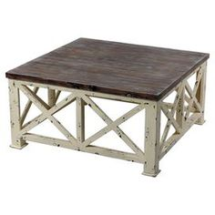 "Distressed wood coffee table in cream and brown with x-shaped base panels.   Product: Accent tableConstruction Material: WoodColor: Cream and brownDimensions: 18.5"" H x 35.5"" W x 35.5"" D"