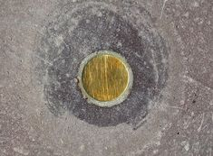 Walter De maria's art installation 1977. What looks to be an unassuming gold disc set flush into the pavement often mistaken for a dropped coin is actually a brass rod that extends vertically into the earth for 1 kilometre. Titled the vertical kilometre.