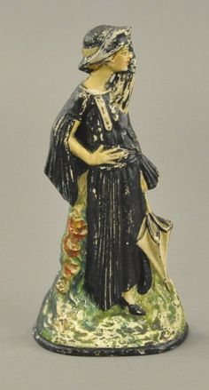 """FLAPPER GIRL DOORSTOP Marked """"Compliments of Toledo Stove Co.,"""" depicts fashionably attired flapper girl in layered dress and umbrella In hand, very elegant design, beautiful and desirable . Antique Iron, Vintage Iron, Knobs And Knockers, Iron Doors, Door Stop, Elegant, Cast Iron, Don't Forget, Bookends"""