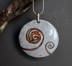 This is a handmade enamel necklace made by me. It is 2 inches in diameter and has a lovely design on the surface. The bail is in Sterling silver and the pendant comes with a sterling 18 inch chain. It is modern and it is unique