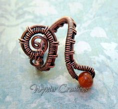 All the elegance and distinctive style of steampunk design shines in the Josephine Copper Wire Wrapped Ring.  This adjustable ring features a stylized handcrafted copper gear, accented by a bright red