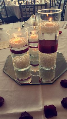 Gorgeous centerpieces with pearls and floating candles. Add a mirror tile for double the effect!