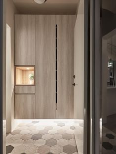 The entryway has tall storage closets that float above a tiled floor, thats highlighted with the use of hidden LED lights. A small open shelf with a light is an ideal place for keys and wallets.