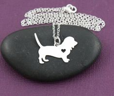 Basset hounds are easily lovable with their big puppy dog eyes, drooping ears, and patient demeanor. This pendant can show your love for the breed, featuring a heart cutout on the basset hound shaped