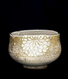 Tea bowl with design of chrysanthemums  early 19th century    Nin'ami Dohachi , (Japanese, 1783-1855)   Edo period     Stoneware with white slip and iron pigment under clear glaze, gold leaf over glaze  H: 8.8 W: 12.8 D: 12.8 cm   Kyoto, Japan . Thick white-clay solution was used to model the relief decoration of chrysanthemum blossoms, a floral motif closely associated with autumn through winter. Perhaps this bowl was made for a New Year's chanoyu gathering.