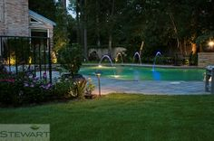 Don't be afraid to add colorful lights to the pool for a more playful nighttime look. #StewartLandDesigns