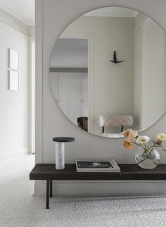 How about a large circular mirror for added interest to the hall?