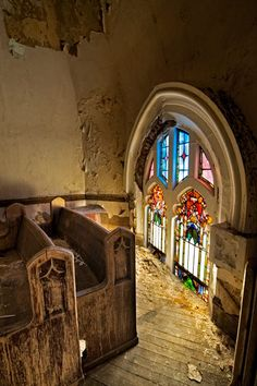 Natural sunlight seeps into the decaying church through the stained glass windows on the balcony.