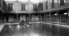 Enkele mannen midden in het zwembad van het badhuis aan de Heiligeweg in Amsterdam, waar ze zich aan een kabel vasthouden. Nederland, 1915.