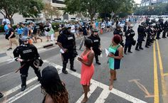 Protesters speak at police officers as fans leave Bank of America Stadium in Charlotte, NC on Sunday, September 25, 2016. The Carolina Panthers hosted the Minnesota Vikings in NFL action.