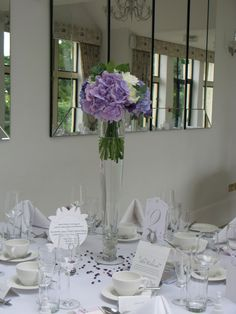 Tall glass vases filled with a tied posy of hydrangea, dahlia and lisianthus.