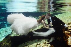 Underwater magic in a cenote in a trash the dress shoot in the Riviera Maya. Mexico wedding photographers Del Sol Photography.