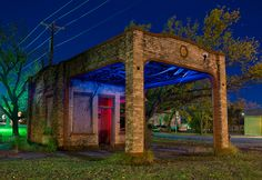 The shell of an abandoned gas station (possibly a Magnolia station) stands by the side of the road in Ferris, Texas.