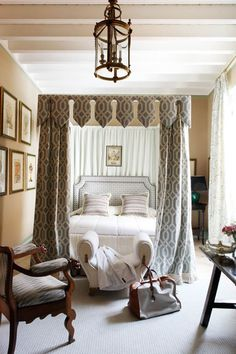 """Guest Bedroom with an Antique-y """"Feel"""" to these shield-shaped bed draperies created out of a new fabric interpretation, possibly inspired by patterns of shadows from iron gates. . Canopy bed upholstered in Gastón y Daniela fabric; 19th-century Colonial Spanish armchairs; Walls upholstered in a camel velvet from Lorenzo Castillo for Gaston & Daniela. Photo from Veranda"""