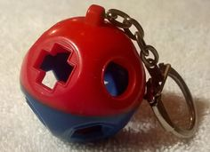 Shape O Ball Blue and Red mini shape sorter kid toy. Made of plastic. There is only one yellow shape sorter inside the key chain. This is a used item.
