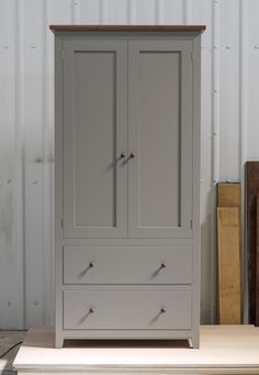 Larder cupboard handpainted in Farrow & Ball Estate Egshell - 'Mole's Breath'. Tulip wood carcass with birch ply panels and shelves. Dovetailed oak drawers on high quality soft close runners. Oak spice racks. Solid brass hinges and adjustable brass shelf supports. Solid walnut cornice and knobs.