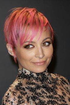 Nicole Richie, in typical Nicole Richie fashion, has a new look. But this one is a bigdeparture, it's a pixie cut. Of course, Nicolebeing Nicole, her undone pixie also happens to be fuchsia, of course.  Nicole showed off her new look in Los Angeles last nightat Tom Ford's Fall 2015 fashion show.  We love this look on Nicole, it plays up her wide eyes and highlights her cheekbones. Wenoticeshe added black liner to her lower waterline, which plays up the gamine look of the short cut.