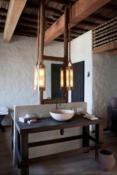 Love this rustic bathroom - look at the texture of the walls and those beams! The Salvage Company