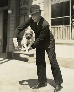 Humphrey Bogart and Zero, the dog, performing a trick in a scene from 'High Sierra' (1941)