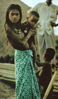 A village girl near Chiringa, Bangladesh carries a smaller child while her mother cooks and sews National Geographic | September 1972