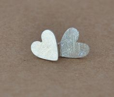 Silver Heart stud earrings designed and made in my studio using textured sterling silver. As this item is handcrafted the hearts may vary a little but this makes them as individual as the person wearing them. Approx 6mm in diameter. These earrings come complete with a Silver