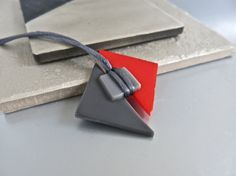 Modern, sleek, hand-made fused glass necklace for those who like geometric design.  Medium gray and red triangles and light gray square were fused