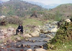 Self-portrait on the Karolitskhali River, ca. 1910. Prokudin-Gorskii in suit and hat, seated on rock beside the Karolitskhali River, in the Caucasus Mountains near the seaport of Batumi on the eastern coast of the Black Sea.