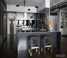 In the kitchen of George Nunno's New York loft, the custom cabinetry is ebonized oak topped with Nero Marquina marble, the black and brass barstools are by Milo Baughman and the iron sculpture was found in a Paris flea market. Tour the rest of Nunno's sexy and stylish Manhattan loft here.