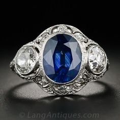 This exquisite and impressive jewel, in glorious blue & white, dates from the first or second decade of the twentieth century and thus displays a combination of Edwardian and Art Deco design characteristics. A rich cornflower blue oval sapphire, weighing 3.00 carats, is flanked by a sizable pair of old mine-cut diamonds, together weighing 1.25 carats, and is embellished all around with small round diamonds with decorative hand piercing, engraving and milgraining in platinum