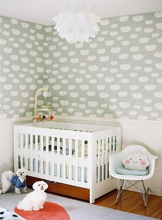 Adorable nursery features upper walls clad in Ferm Living Cloud Wallpaper - Mint and lower walls painted white finished with a white chair rail lined with a Baby Mod - ParkLane 3-in-1 Baby Convertible Crib, Amber and White adorned with a Winnie The Pooh Mobile next to a white Eames Rocker illuminated by an Artichoke Pendant Lamp.