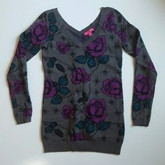 "Betsey Johnson Rose Spider Sweater Dress Wonderful Betsey Johnson sweater v neck and v back cut neck line with long sleeves. Tunic dress that is grey with purple roses that have curvy stems with leaves that are more of a aqua green blue and these flowers are next to spiders! 100% cotton and excellent condition. This is a very rare print. Retails for $298. 29"" long and 34"" across the chest, material does have some stretch. Works for a classy Halloween outfit! Betsey Johnson Dresses"