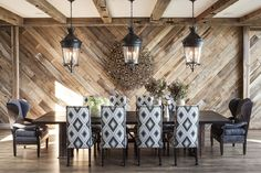 This dining room feels so creative- timber feature wall, patterned chairs with plain carvers, large lanterns.