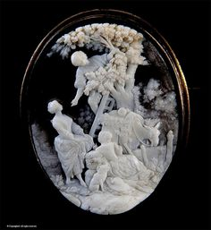A magnificent shell cameo depicting a pastoral-orchard scene with man on ladder handing fruit or nuts to woman with open apron with child and dog looking on and donkey in the background - Italian   c.1830