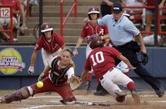 Alabama's Kaila Hunt (10) slides home safely as Oklahoma catcher Jessica Shults, left, takes the throw in the second inning of the second game of the NCAA Women's College World Series softball finals in Oklahoma City, Tuesday, June 5, 2012. (AP Photo/Sue Ogrocki)