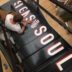 Hand Signwriting the stairs. Typography stairs at Goodwin & Goodwin.