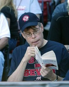 Stephen King reads a novel at a Redsox game.